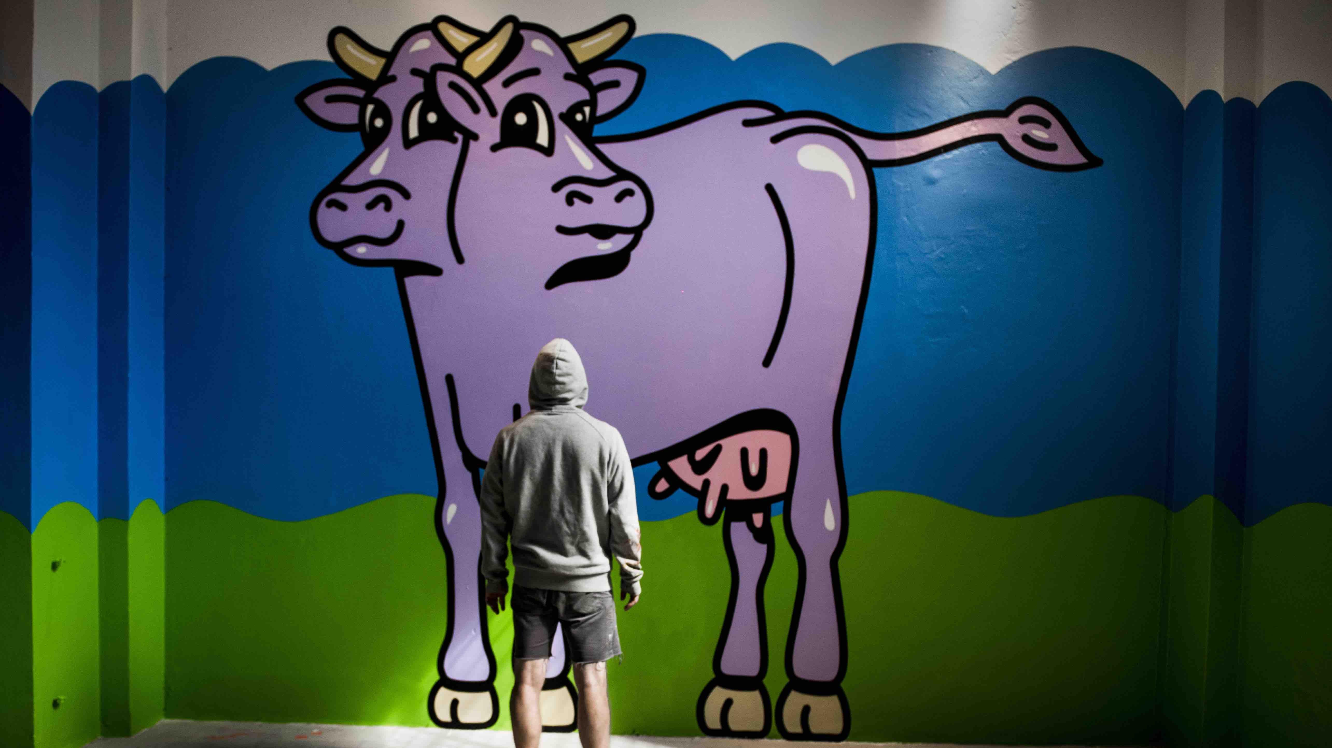 Vi kender ikke til kunstneren HuskMitNavns identitet. Her er han fotograferet foran et af sine graffitiværker med ryggen til kameraet.