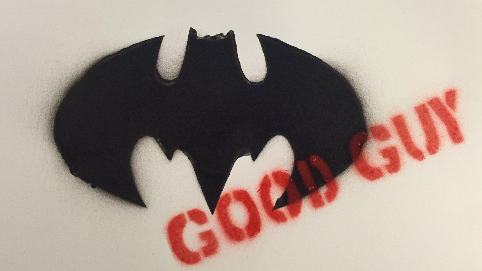 Stencil med sort Batman-logo som motiv og budskabet med rødt.