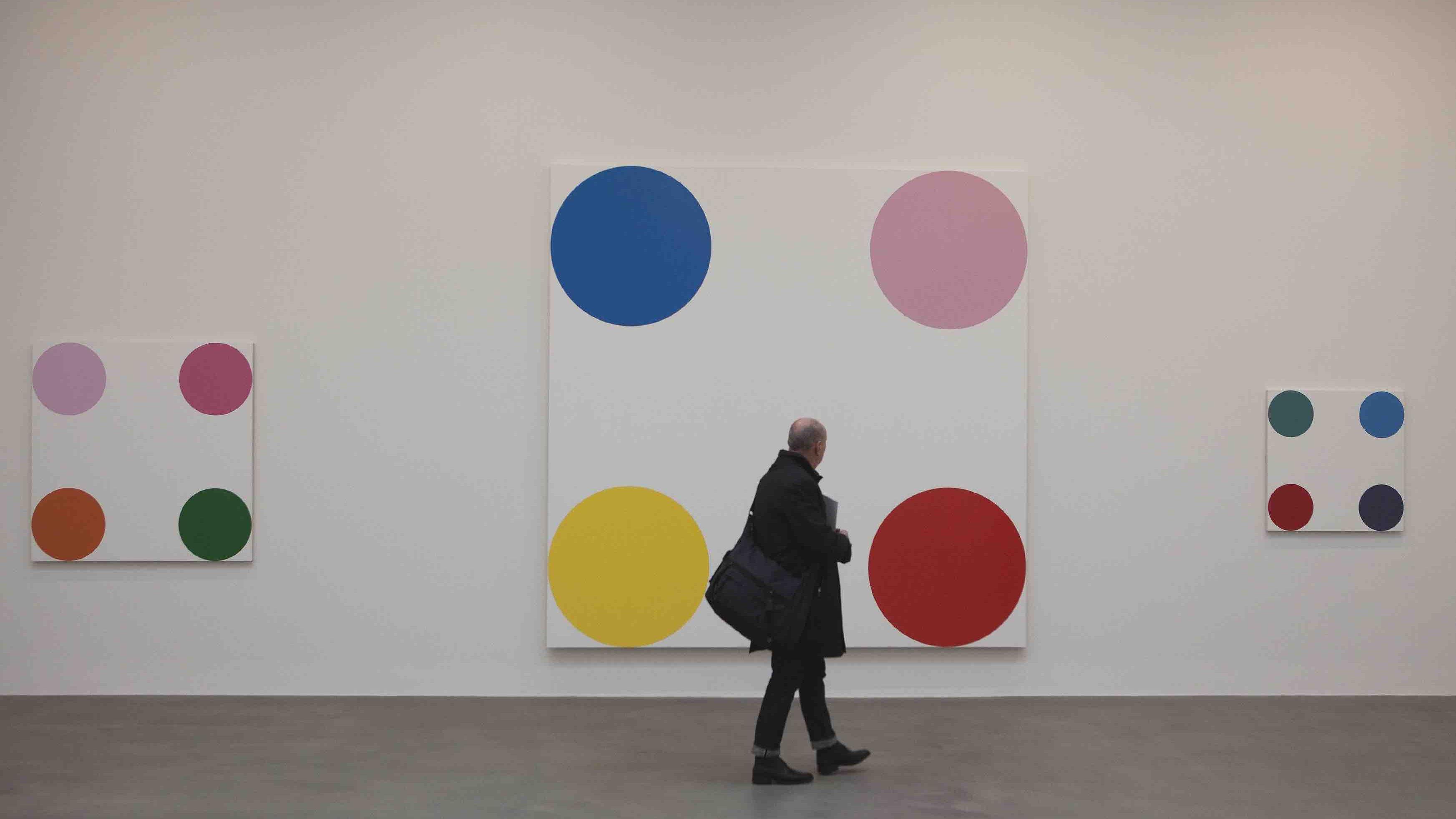 En mand kigger på tre udstillede spot-malerier malet af kunstneren Damien Hirst.