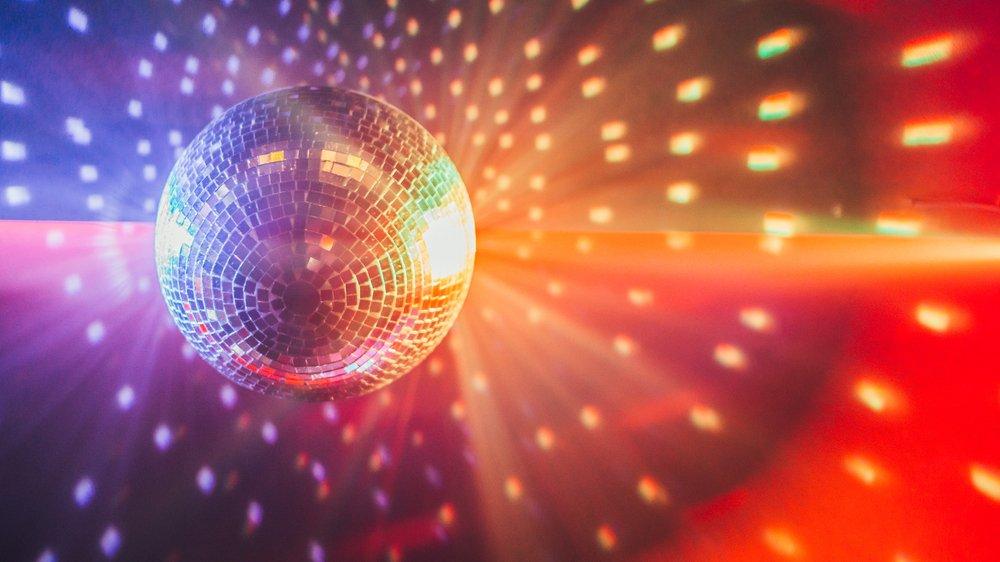 En diskokugle lyser med farvede pletter på væggen.
